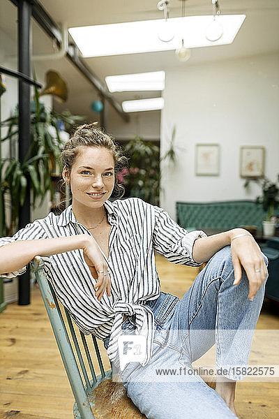 Junge Frau sitzt entspannt auf Stuhl