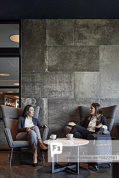 Two businesswomen sitting in arnchairs in hotel lobby talking