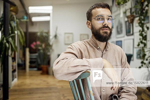 Junger Mann sitzt auf Stuhl und schaut skeptisch in die Kamera