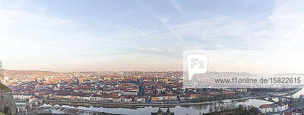 Deutschland  Bayern  Würzburg  Panorama des Himmels über dem Stadtfluss und den umliegenden Gebäuden in der Abenddämmerung