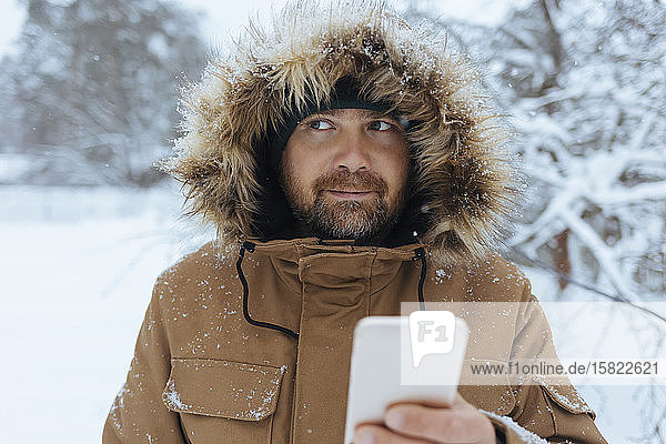 Portrait of pensive man with cell phone in winter