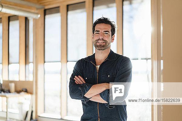 Porträt eines am Fenster stehenden lächelnden Geschäftsmannes in einem hölzernen Großraumbüro