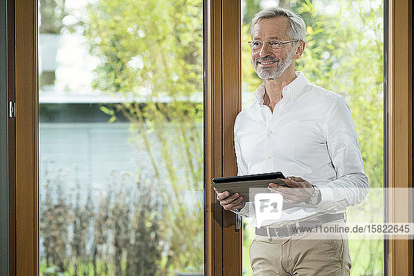 Smiling senior man with grey hair in modern design living room standing at window holding tablet