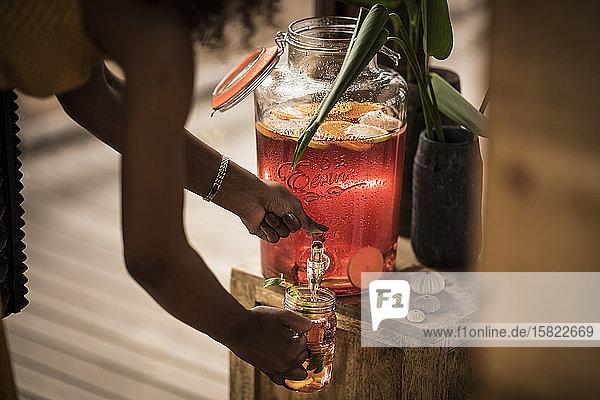 Nahaufnahme einer Frau  die frisches Eisteegetränk in ein Glas gießt