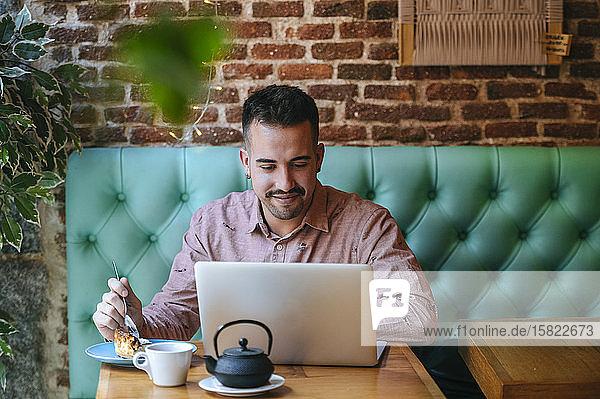Mann in einem Café mit Laptop