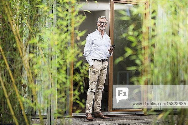 Älterer Mann mit grauen Haaren steht vor seinem modernen Design-Haus mit Smartphone