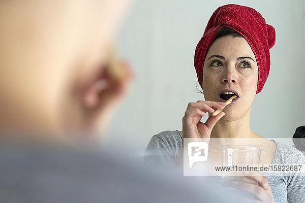 Porträt einer Frau mit in ein Handtuch gewickeltem Kopf beim Zähneputzen mit einer hölzernen Zahnbürste Porträt einer Frau mit in ein Handtuch gewickeltem Kopf beim Zähneputzen mit einer hölzernen Zahnbürste