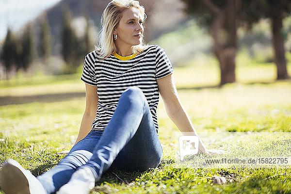 Blond lächelnde Frau  die auf einer Wiese sitzt und seitwärts in einen Park schaut