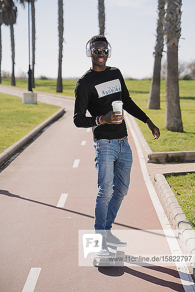 Stilvoller junger Mann hört Musik mit Kopfhörern und fährt Skateboard
