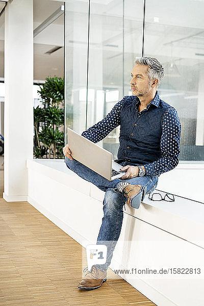 Gelegenheits-Geschäftsmann sitzt auf der Fensterbank eines Bürogebäudes und benutzt Laptp