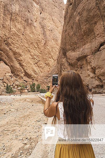 Rückansicht einer jungen Frau  die mit einem Smartphone fotografiert  Ouarzazate  Marokko