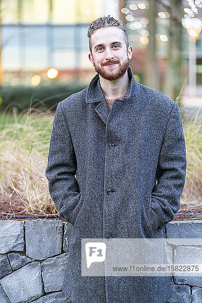 Porträt eines lächelnden jungen Mannes in der Stadt Porträt eines lächelnden jungen Mannes in der Stadt