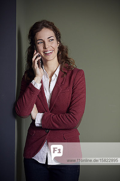 Portait of smiling businesswoman on the phone in office