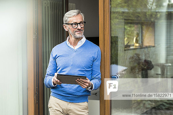 Smiling senior man with grey hair standing in front of his modern design home holding tablet