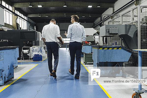 Rückansicht von zwei Männern  die in einer Fabrik gehen und sprechen