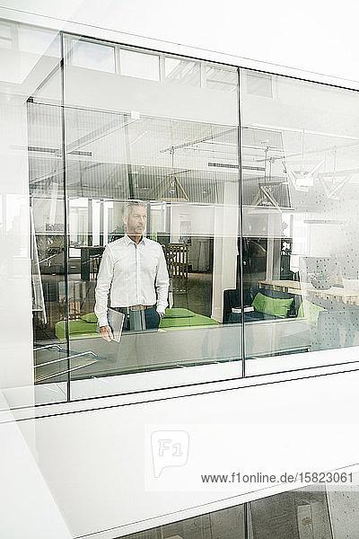 Ein reifer Geschäftsmann schaut aus dem Bürogebäude und hält einen Laptop