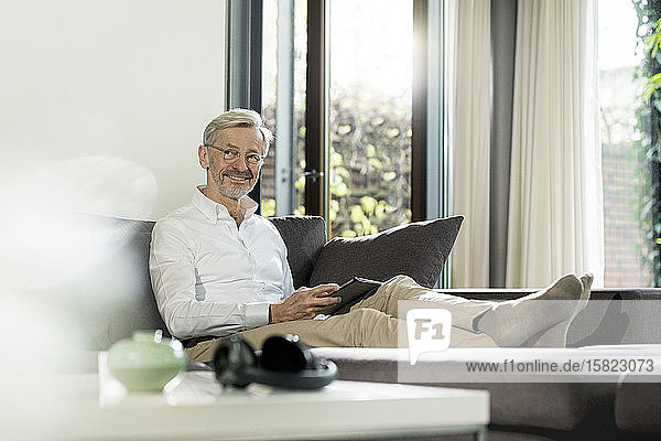 Smiling senior man with grey hair in modern design living room sitting on couch holding tablet