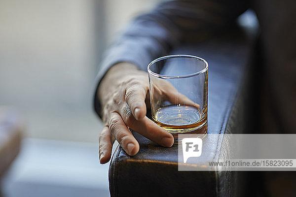 Nahaufnahme eines Mannes mit Whiskeyglas auf der Armlehne eines Lederstuhls