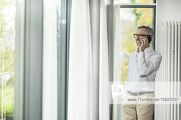 Smiling senior man with grey hair talking on the phone in modern design home with large windows