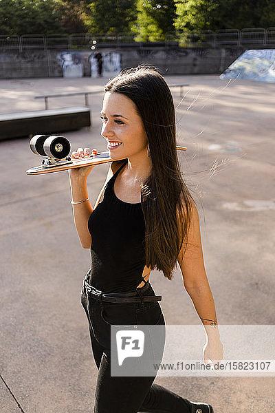 Junge Frau mit Skateboard auf der Schulter in einem Skatepark