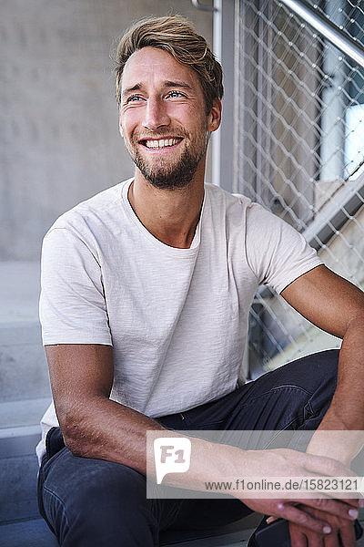 Porträt eines lächelnden jungen Mannes mit weißem T-Shirt  der auf einer Treppe sitzt