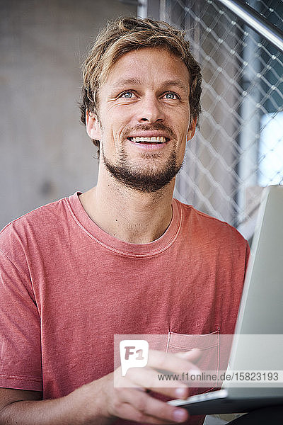 Portrait of young man wearing t-shirt using laptop