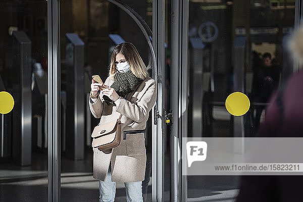 Woman with face mask  using smartphone at subway station