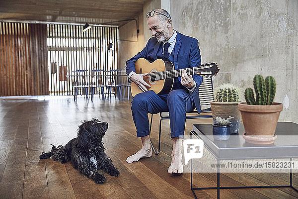 Leitender Geschäftsmann sitzt im Büro und spielt Gitarre für seinen Hund