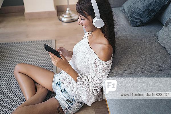 Lächelnde junge Frau  die mit Kopfhörern Musik hört und zu Hause im Wohnzimmer auf dem Boden sitzt