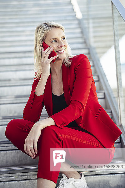 Blond businesswoman wearing red suit and using smartphone  sitting on stairs