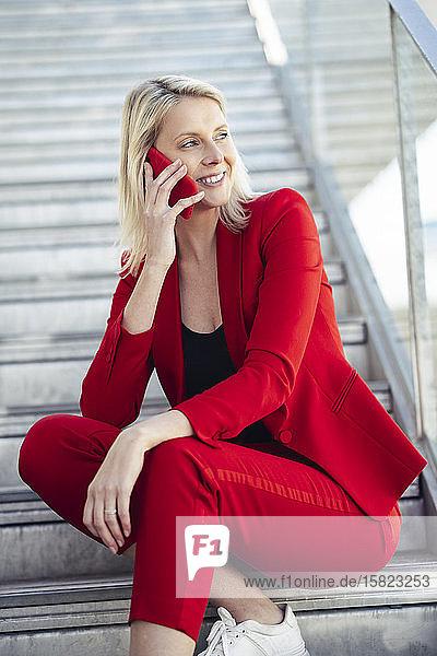 Blonde Geschäftsfrau in rotem Anzug und mit Smartphone  auf der Treppe sitzend