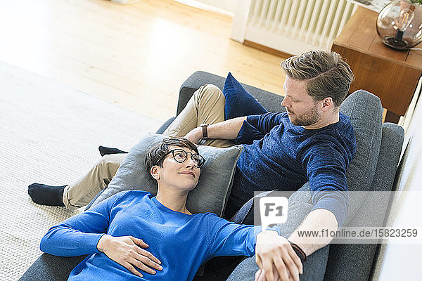 Casual couple relaxing on lounge couch in their modern living room