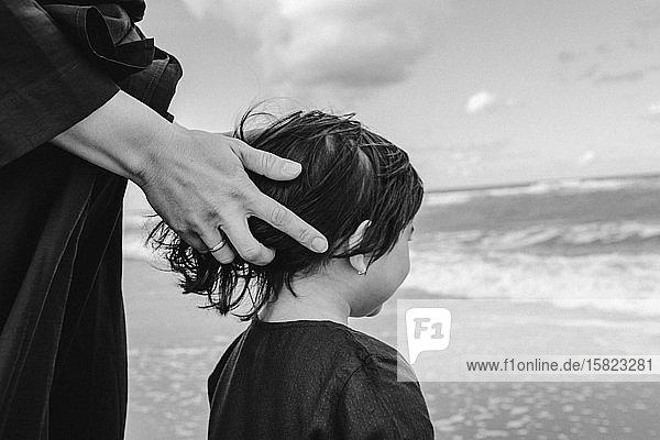 Die Hand der Mutter berührt das Haar der kleinen Tochter am Strand