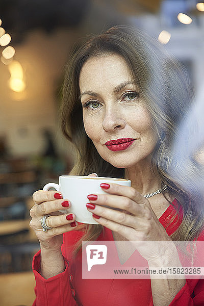 Portrait of mature woman with cup of coffee behind windowpane