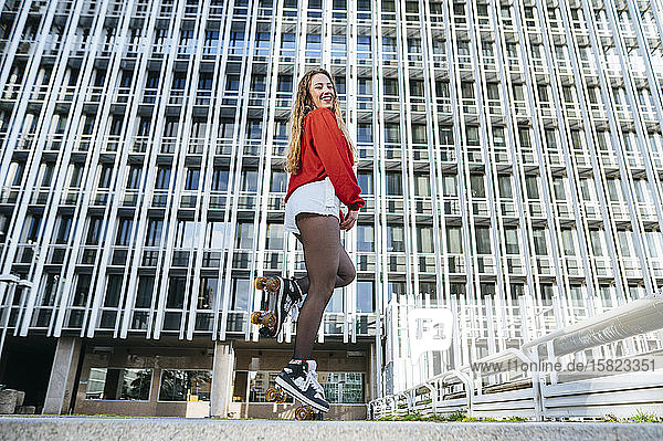 Porträt einer glücklichen jungen Frau  die auf Rollschuhen in der Stadt balanciert
