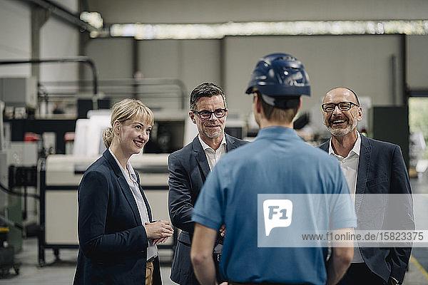 Lächelnde Geschäftsleute sehen Arbeiter in einer Fabrik an