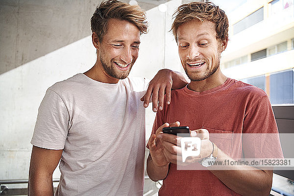 Two happy young men sharing smartphone