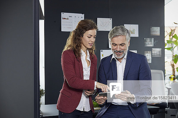 Businessman and businesswoman working together on tablet in office