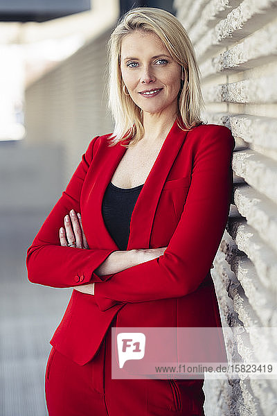 Blond smiling businesswoman with arms crossed wearing red suit and looking at camera