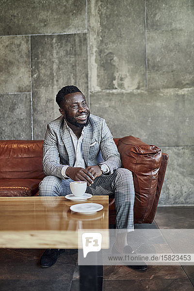 Smiling businessman relaxing in hotel lobby