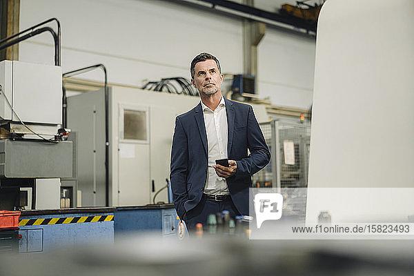 Reifer Geschäftsmann mit Mobiltelefon in einer Fabrik
