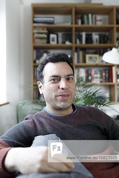 Porträt eines reifen Mannes  der zu Hause auf der Couch sitzt