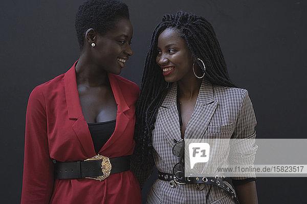 Zwei junge Frauen vor einer grauen Wand