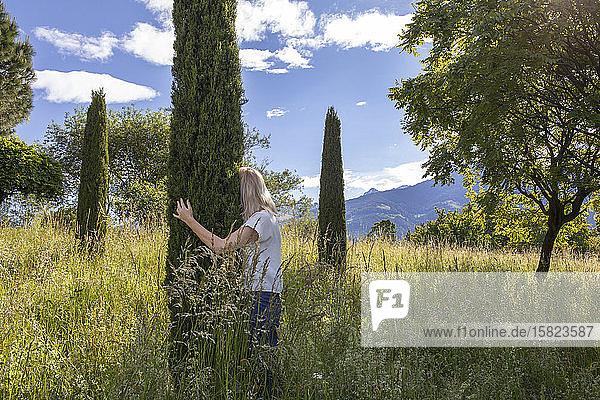 Woman standing in meadow  hugging cypresse