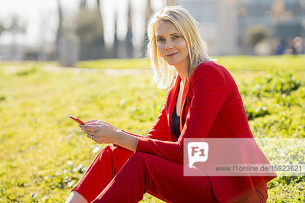 Blond businesswoman wearing red suit using smartphone and sitting on a meadow