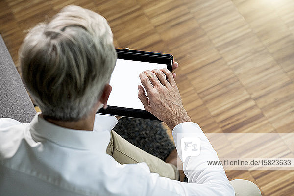 Senior man using tablet at home