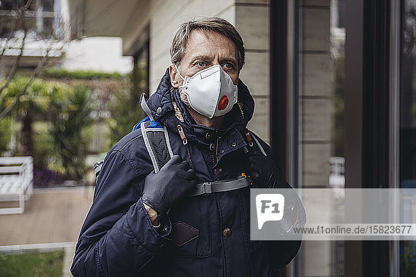 Matuer man commuting in the city  wearing protective mask