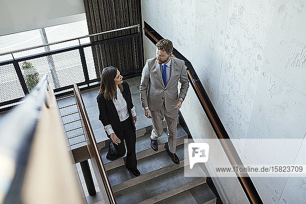 Businessman and businesswoman walking down staircase