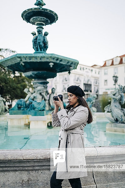 Young female traveller with camera at Rossio square's fountain  Lisbon  Portugal