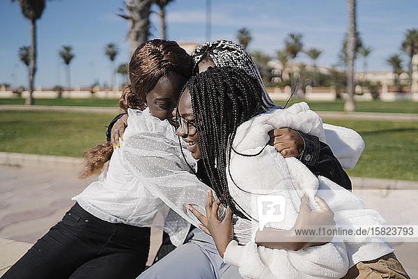 Glückliche Teenager-Freundinnen umarmen sich im Freien